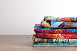Quilts stacked on wooden table