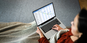 Woman using a timesheet app in Australia on her laptop